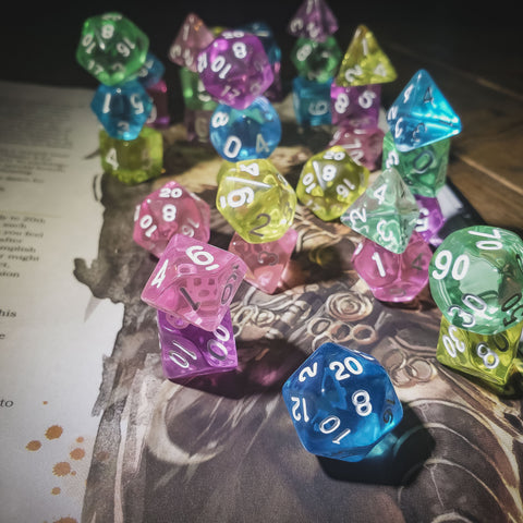 Image Description: A photograph of several sets of different colored dice on top of a dungeons and dragons book. The dice are brightly colored and mostly transparent. End description.