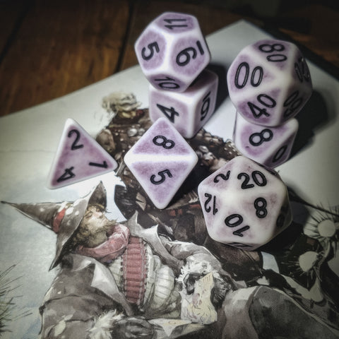 A photo of faded purple dice with black numbers on top of a drawing of a man in a wizards hat and an armored skeleton