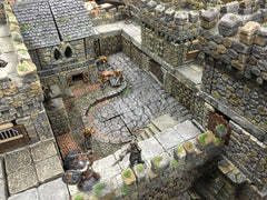 A photo of 3-dimensional terrain used for dungeons and dragons. It looks like a miniature castle, with small figures of adventurers dispersed around it.