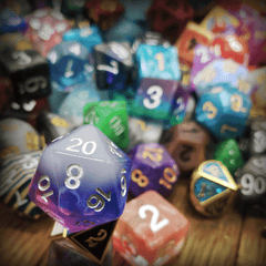 A photo of an assortment of dice, in various colors, sizes, and numbers of sides.