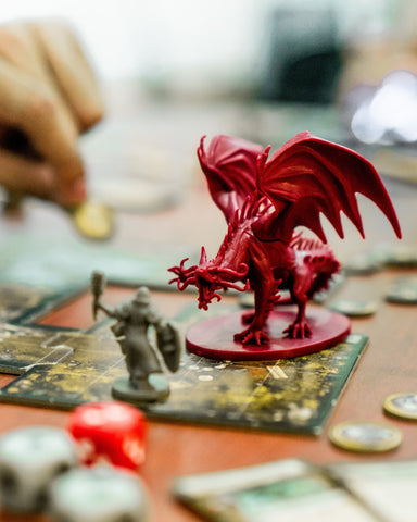 A photo of a dragon miniature placed as though in combat with several warrior miniatures, surrounded by dice and map tiles. A hand can be seen in the background.