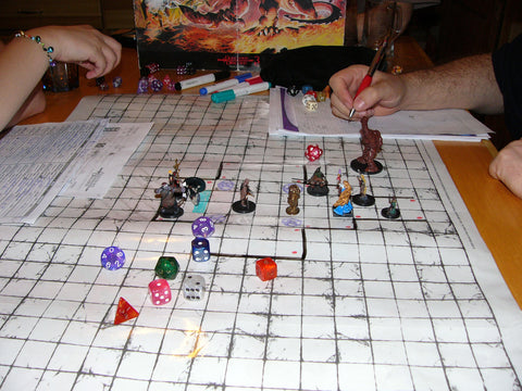 A photo of a game of Dungeons and Dragons. There is a white grid on the table with several miniatures and dice laid out on top of it, with a couple of arms and a DM screen in the background.