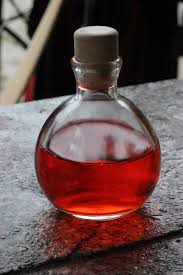 A photo of a potion bottle filled with red liquid, implied to be a love potion.