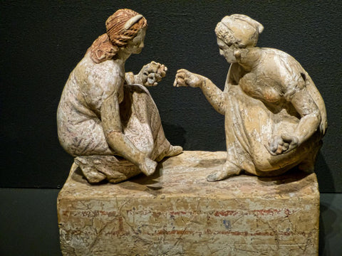 A photo of an ancient greek statue, which depicts two women kneeling, holding knuckbone dice. They are apparently playing some kind of gambling game with them.