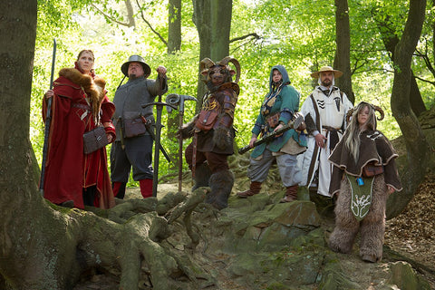 A photo of several people in fantasy character costumes in the woods, presumably preparing for a LARP