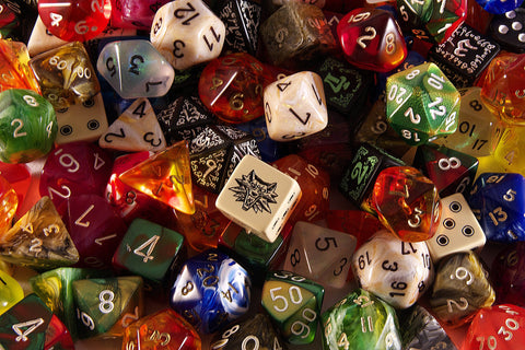 A photo of a large pile of gaming dice, of various types, colors, and sizes. The central die is has the image of a wolf on the top-facing side.
