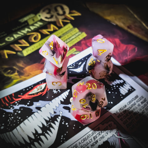 A photo of s set of gaming dice in red, white, and black swirls with gold numbers. The dice are stacked on an old gaming magazine.