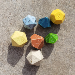 A photo of several dice in multiple colors - they are old, with worn edges and uninked numbers.