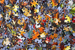 A photo of a pile of standard-cut jigsaw puzzle pieces. They are a number of different colors