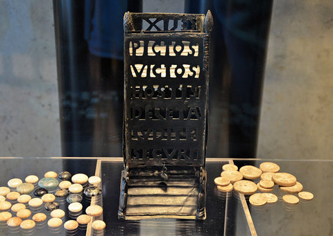 A photo of an ancient roman dice tower, engraved with several latin words and surrounded by ancient bone dice