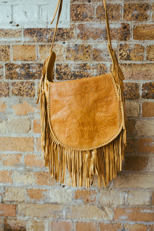 a bohemian style tassel leather bag with cow skull design
