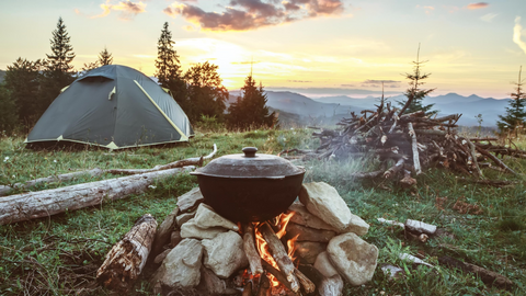 Cooking over campfire overlooking view of the mountains