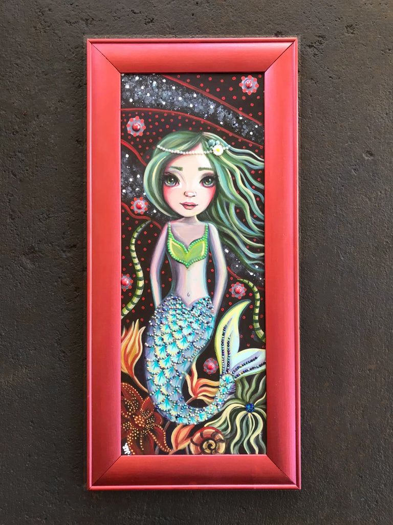 A whimsical mermaid painting in a rose gold coloured wood frame. Lots of rhinestones and sparkles added.