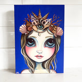 A painting on canvas of a mermaid wearing a crown on a royal blue background