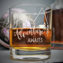 Engraved glass with mountain design and text that reads adventure awaits