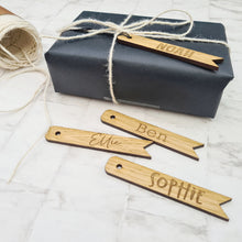 Personalised wooden gift tags, engraved with names attached to a black wrapped parcel tied up with string