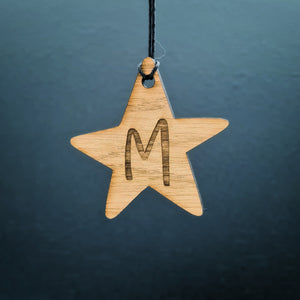 Christmas star shaped personalised gift tag. Made from wood and engraved with the initial of your choice