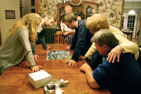 family assembling a jigsaw puzzle together - The Missing Piece Puzzle Co