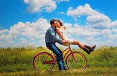 Wedding Guest Book Puzzle in Bright blue of couple kissing on a bicycle. The Missing Piece Puzzle Company