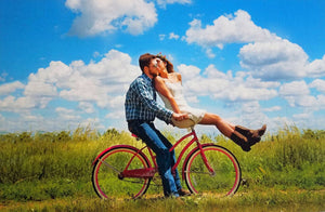 Bright Wedding Guest Book Puzzle photo of couple riding bike kissing with large puzzle pieces.