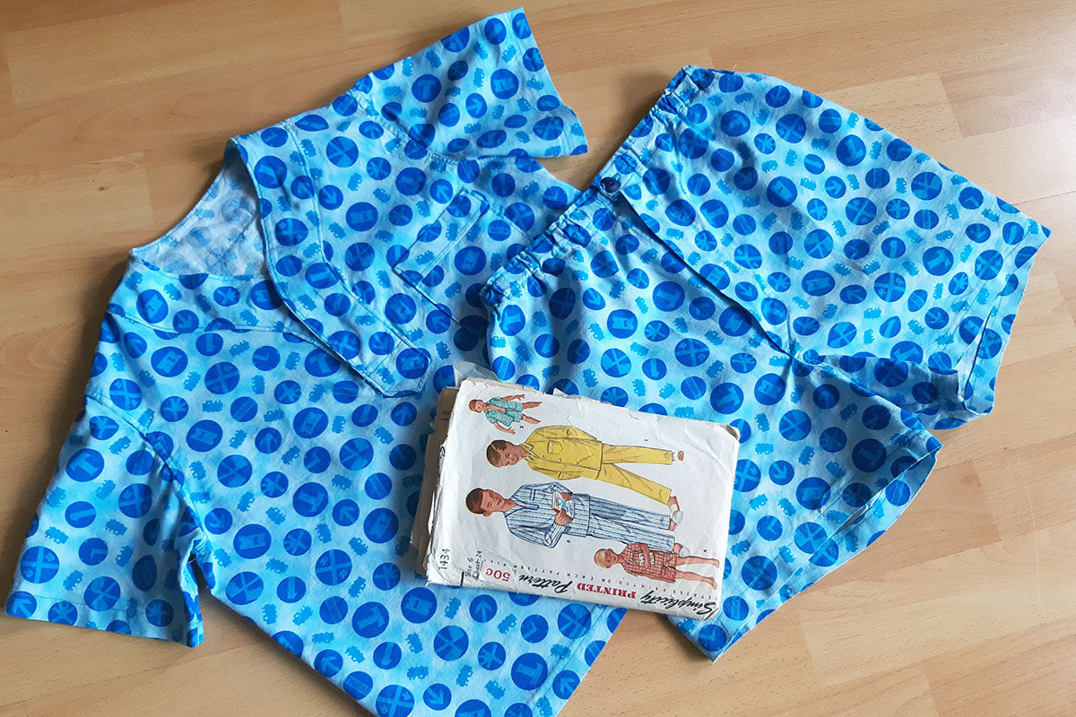 Flat lay of handmade boys summer pajamas in blue print with vintage sewing pattern resting on top