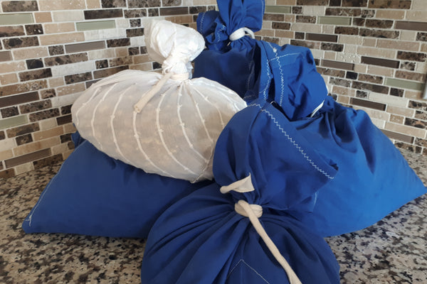 a pile of blue and white bags bulging with food