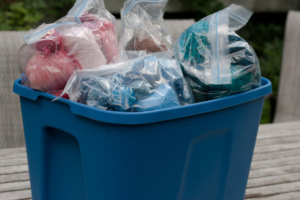 Blue rubbermaid tub overflowing with ziploc bags full of yarn scraps, sorted by colour