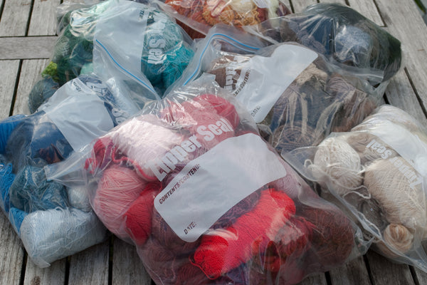 Large ziploc bags full of yarn scraps, sorted into colours
