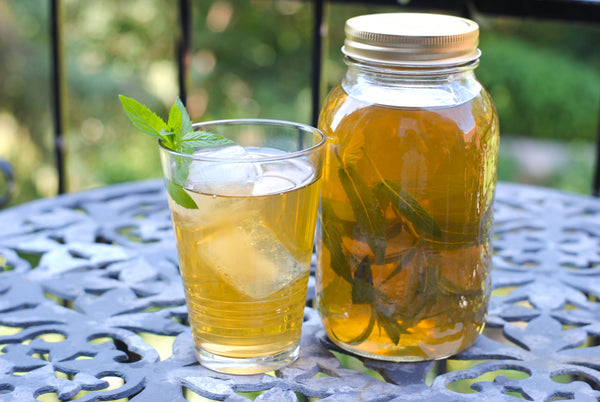 Glass of green iced mint tea beside mason jar