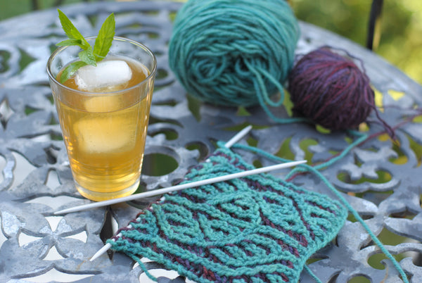 Glass of iced tea next to knitting