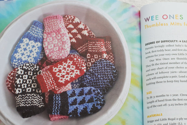 Bowl of colourful baby mittens featuring graphic patterns