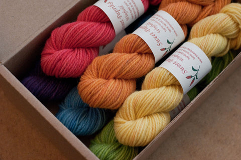 A set of six mini-skeins of Winfield yarn in rainbow colours presented in a cardboard box