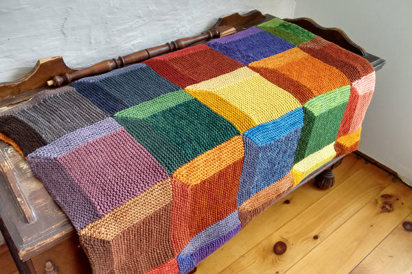 colourful knit attic windows blanket folded neatly and lying across a cedar chest
