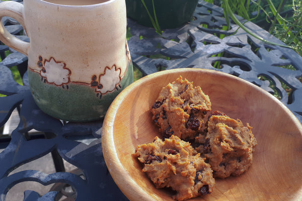 Wooden bowl with three chickpea cookies next to mug of tea