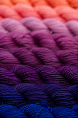 Row of purple gradient yarn skeins all lined up from dark to light