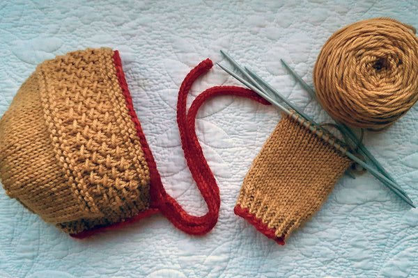 Handknit baby bonnet and legwarmers with pomegranate-dyed yarn