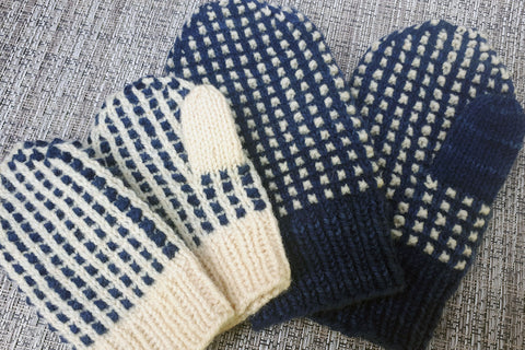 Two pairs of mittens, adult pair is dark blue with natural contrast, child's pair has colours reversed