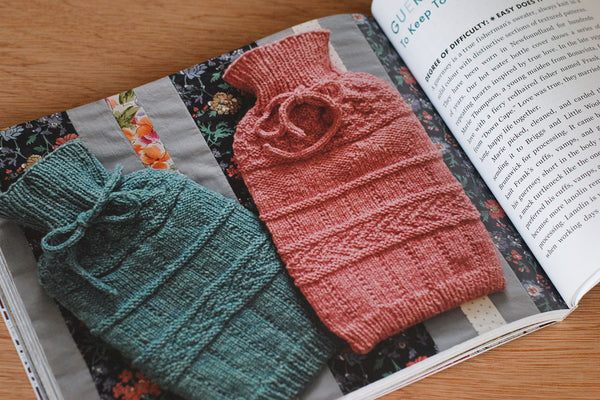 Book open to show a photo of two knit hot water bottle covers in a Guernsey style
