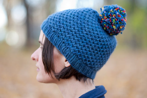 Hanabi blue hand-knit hat in honeycomb brioche pattern with a multicoloured pompom