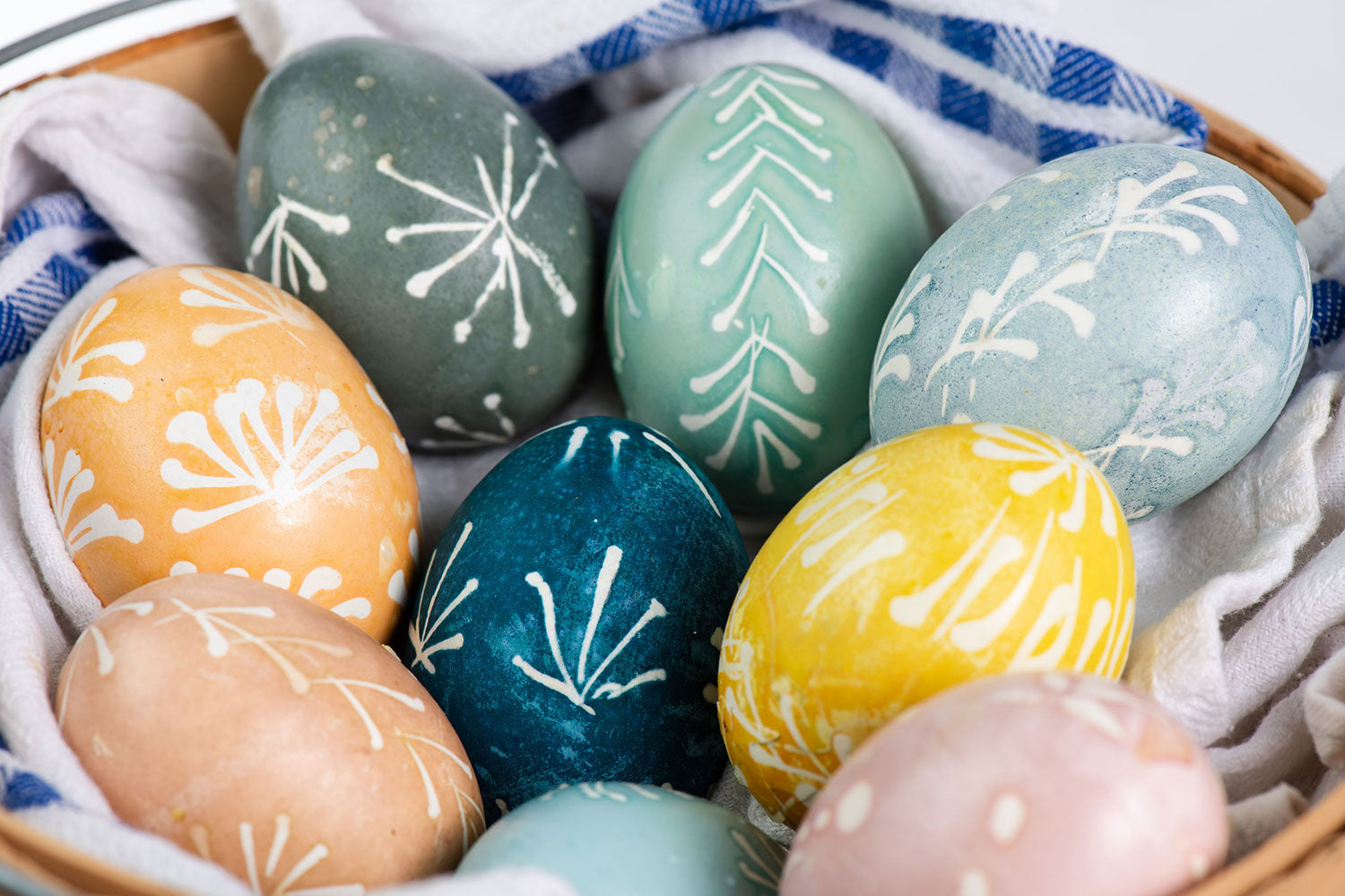 Traditional Lithuanian batik Easter eggs dyed with natural dyes presented in basket lined with tea towels