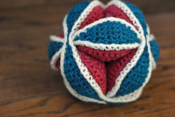 Amish puzzle ball in red, white, and teal