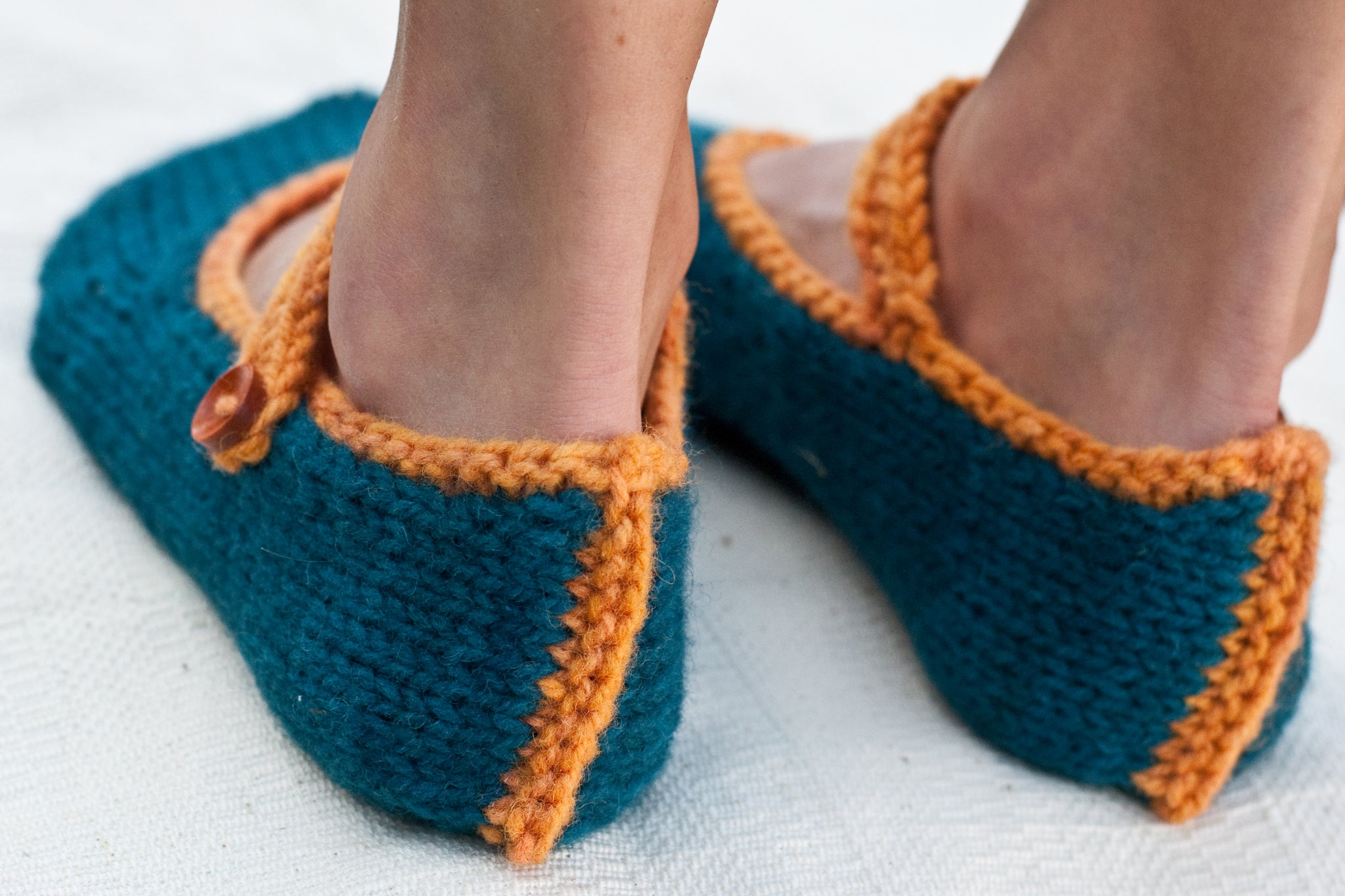 woman's feet wearing hand-knit slippers shown from back and focused on heel seam detail in contrast colour