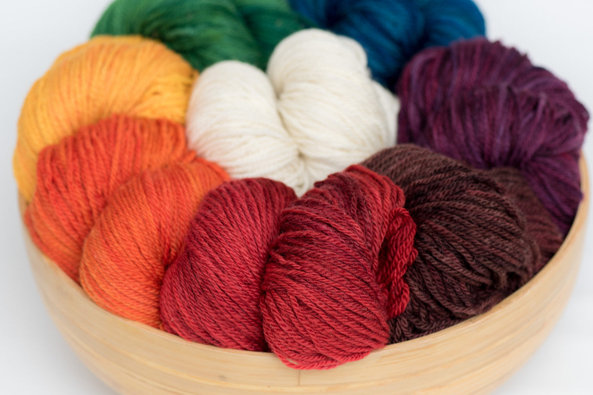 Several skeins of brightly coloured Norwood yarn in a wooden bowl