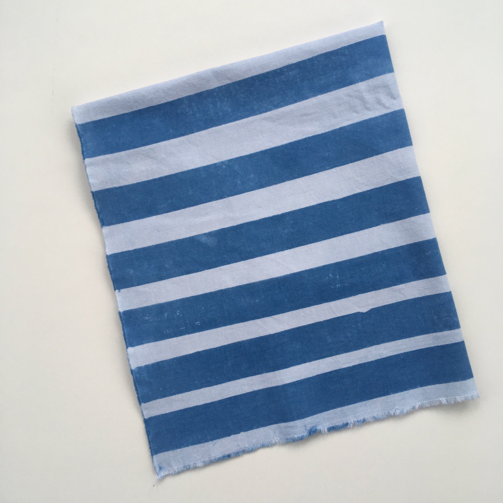 Fabric example dyed with clay resist: deep indigo blue with white stripes of varying width