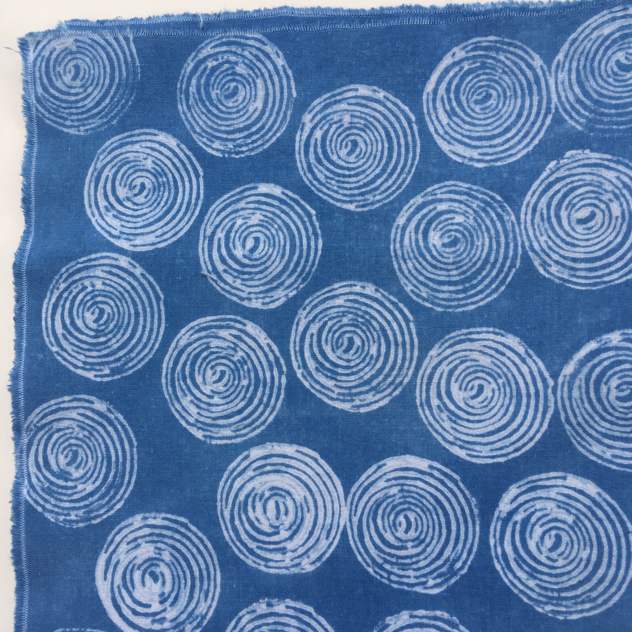 Fabric example dyed with clay resist: deep indigo blue with circular pattern in white.