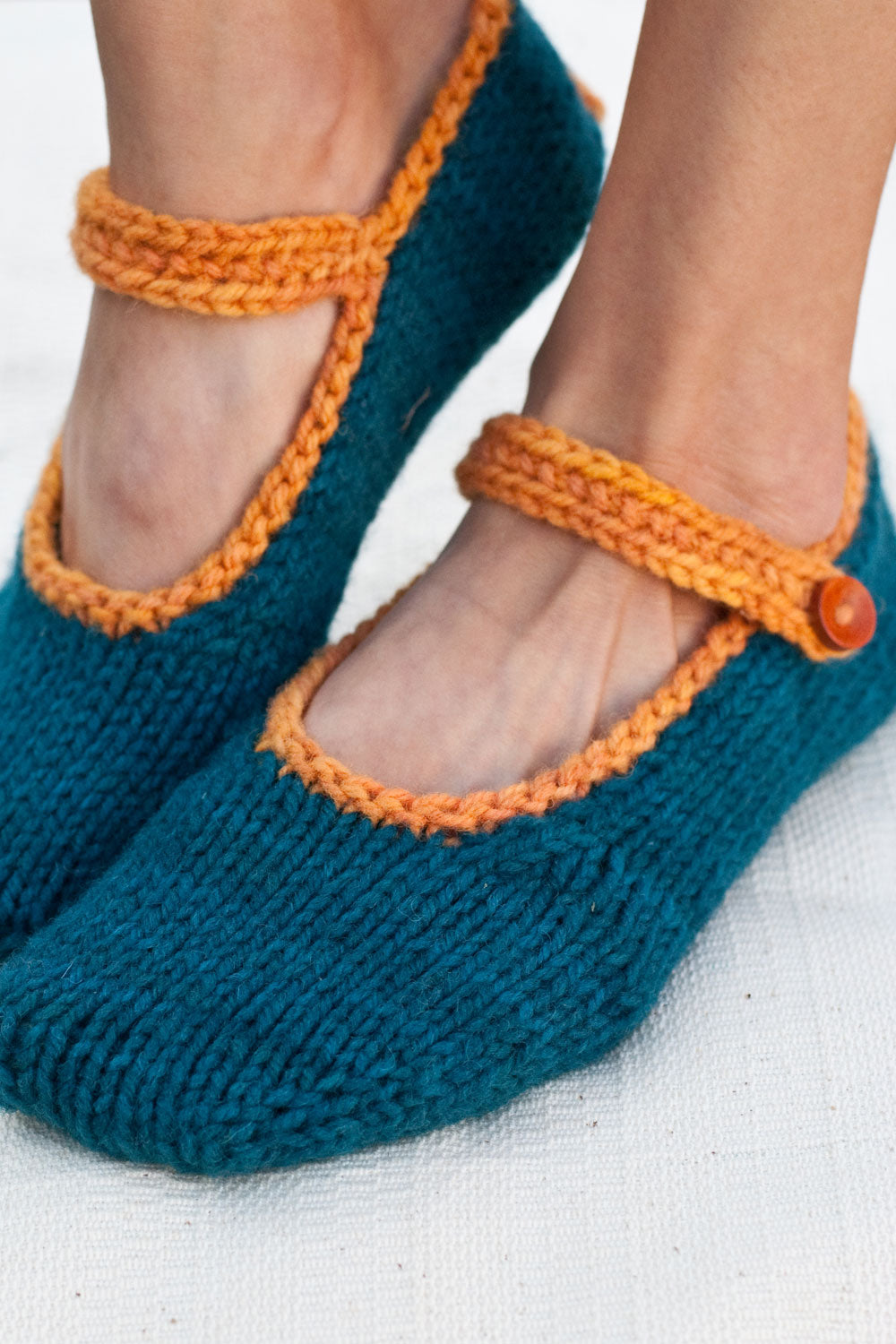 woman's feet wearing dark teal hand-knit slippers with bright orange trim, an ankle strap and wooden buttons