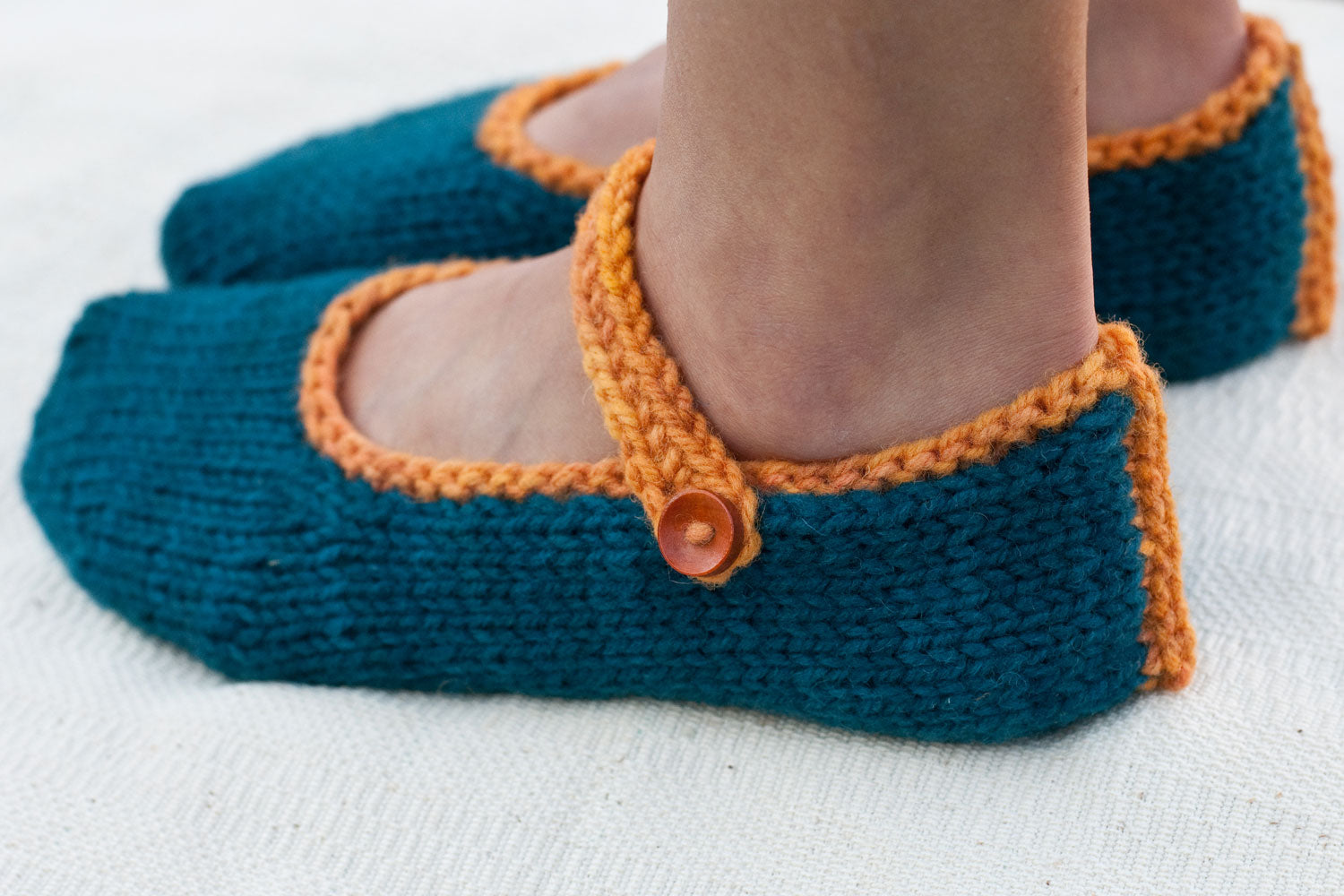 left side of woman's feet in hand-knit slippers showing button and strap detail