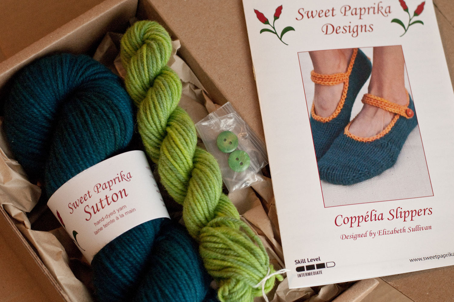 open cardboard box with kit components: pattern, large skein, mini skein and buttons