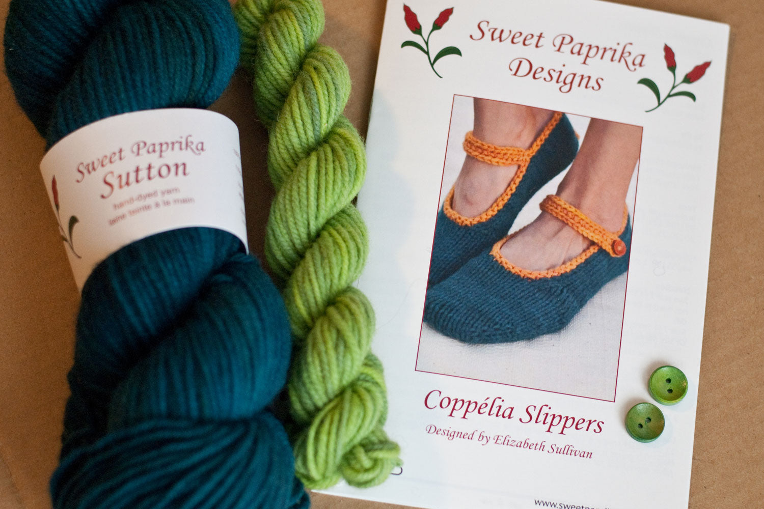 Kit components: knitting pattern, bulky yarn in teal and bright green, green buttons