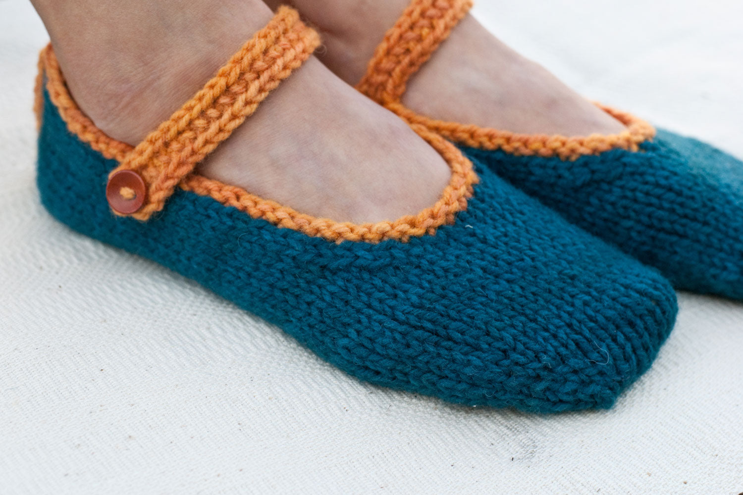 woman's feet wearing sporty hand-knit slippers in dark teal with an orange strap and button
